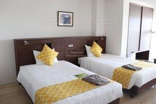黄色のクッションのあるホテルのベッドルームの写真・画像素材[3499209]