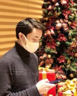 クリスマスツリーの前でスマホ片手に恋人を待つマスク姿の男性の写真・画像素材[3920709]