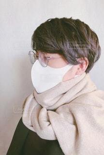 メガネをかけてマフラーを首に巻いたマスク姿の20代男性の写真・画像素材[4161363]