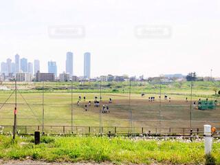 休日の多摩川グラウンドで野球の練習試合をする青少年たちの写真・画像素材[4283155]
