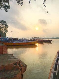夕日に染まるガンジス川と岸辺に停泊する小舟(ボート)の写真・画像素材[4359888]