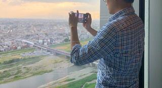 高層ビルの最上階から景色をスマホで撮影する男性の写真・画像素材[4403441]