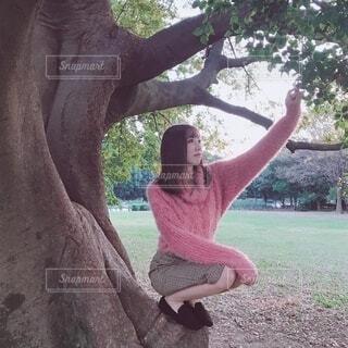 木の幹で黄昏る女性の写真・画像素材[4218156]