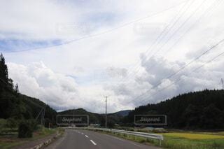 山の側に草のある長い道の写真・画像素材[3688031]