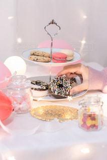 皿の上にケーキを置いてテーブルに座っている女性の写真・画像素材[3533216]