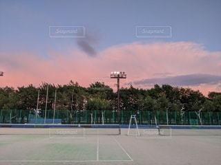 夕焼け空のテニスコートの写真・画像素材[3561663]