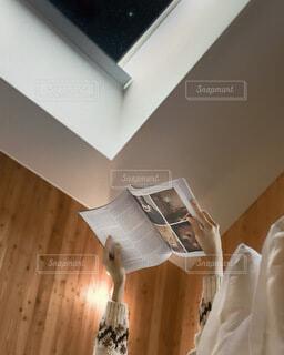 天窓から夜空を眺めて読書の写真・画像素材[4114494]
