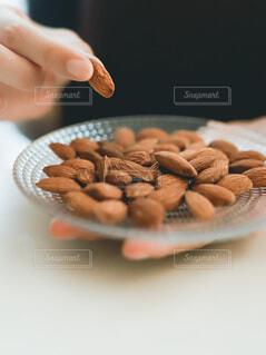 アーモンドを手で摘んでいるの写真・画像素材[4114590]