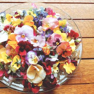 近くに木製のテーブルの上の花のアップの写真・画像素材[763436]