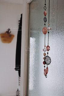 壁に掛かっているネックレスの写真・画像素材[1443970]