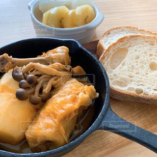 木製のテーブルの上に座っている食べ物のボウルの写真・画像素材[2852349]