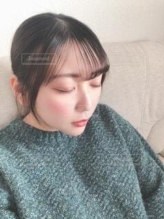 目を閉じているセーターの女性の写真・画像素材[3980634]