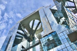 高層ビルに映り込む青い空そして白い雲の写真・画像素材[3691667]
