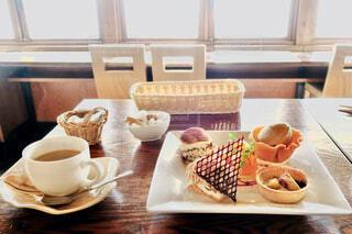 デザート盛り合わせ 木のテーブルと窓からあふれる日の光の写真・画像素材[3728561]