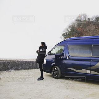 男が車の前に立っています。の写真・画像素材[968354]