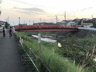 水の体の隣の線路上の大きな長い列車の写真・画像素材[3627721]