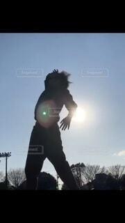 夕日を背にダンスをしている様子の写真・画像素材[3628502]