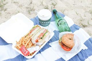 サンドイッチとベーグルでビーチピクニックの写真・画像素材[4439698]