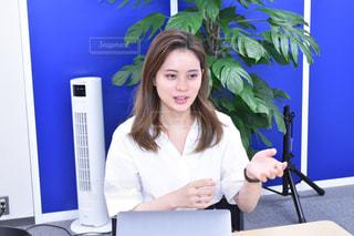 コンピュータの前の机に座っている人の写真・画像素材[2390998]