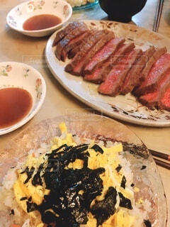 食べ物の皿をテーブルの上に置くの写真・画像素材[3678859]