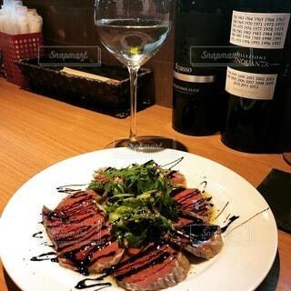 食べ物の皿とテーブルの上のワインのボトルの写真・画像素材[3679351]