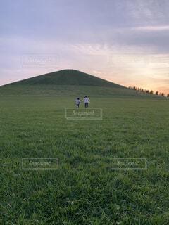 夕焼けに向かって走っていく二人の写真・画像素材[3780841]