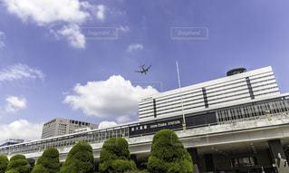 JR新大阪駅と上空を飛ぶ飛行機の写真・画像素材[844585]