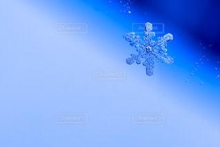 ブルーのグラデーションを背景にした雪の結晶の写真・画像素材[1662701]