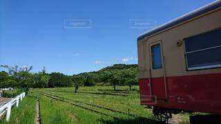 野原の近くの線路上の列車の写真・画像素材[3701953]