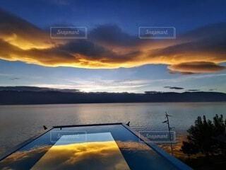水の体に沈む夕日の写真・画像素材[3723424]