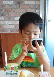 熱心にスマホを操作する子どもの写真・画像素材[3717906]