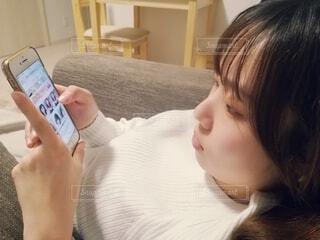 スマホをいじる女性の横顔の写真・画像素材[3724198]