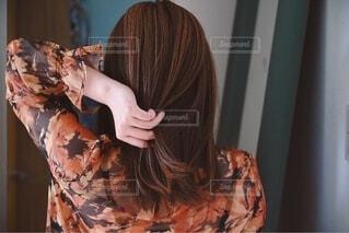 髪の毛を触る女性の後ろ姿の写真・画像素材[3821570]