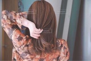 髪の毛を触る女性の後ろ姿の写真・画像素材[3880993]