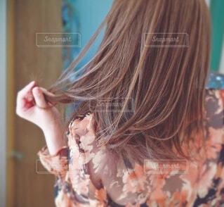 傷んだ毛先を触る女性の後ろ姿の写真・画像素材[3881029]