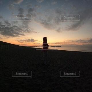 夕日の前に立っている男の写真・画像素材[4020294]