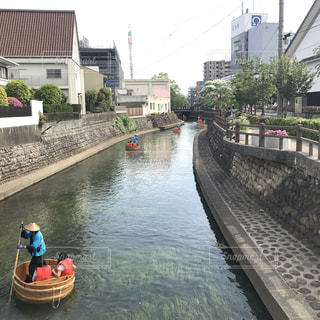 水の中のボートの後ろに乗っている人々のグループの写真・画像素材[2204347]