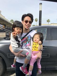 車の前に立っている小さな女の子の写真・画像素材[2391812]