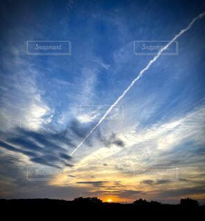ひこうき雲と夕陽の写真・画像素材[4365848]