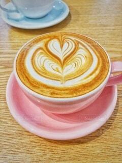 カフェにお出掛け、ピンクのコーヒーカップにハートのラテアートの写真・画像素材[3824122]
