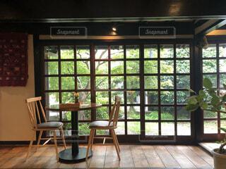 窓の前にダイニングルームのテーブル とあるカフェの写真・画像素材[3747056]