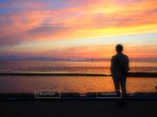 日没の前にビーチに立っている人の写真・画像素材[1284216]