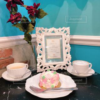 一杯のコーヒーとテーブルの上の花の花瓶の写真・画像素材[1703064]