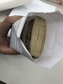 札束の入った封筒を持つ手の写真・画像素材[3770021]