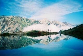 背景に山のある水の体の写真・画像素材[3778899]