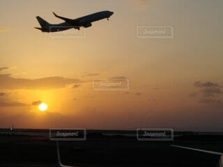 夕日を背に飛び立つ飛行機の写真・画像素材[3904667]