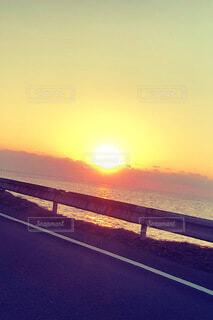 海に沈む夕日と錆びたガードレールの写真・画像素材[4010237]