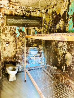 朽ちた刑務所の部屋にあるトイレとベッドの写真・画像素材[4287492]