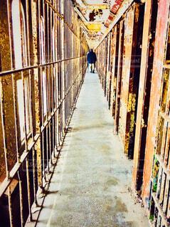 鉄格子が続く刑務所の部屋を見学する男性の写真・画像素材[4292352]