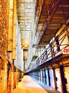 古い建物の長い廊下沿いの鉄格子の部屋の写真・画像素材[4292361]